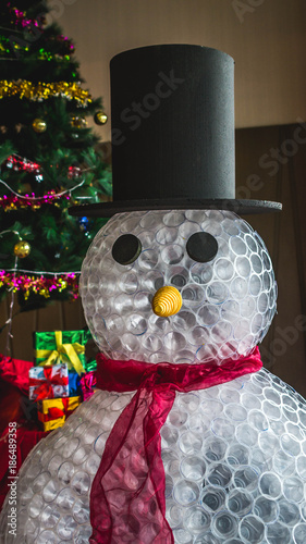 indoor christmas decoration snowman figure made from plastic glass in front of christmas tree