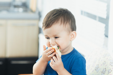 The little boy in the kitchen eating a small pizza
