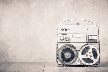 Retro old reel to reel tape recorder front concrete wall background. Vintage style sepia photo