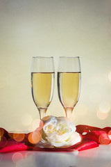 Two glasses with champagne, a white rose flower and a red ribbon. Bokeh