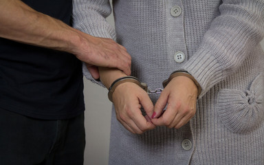 Policeman arrests a criminal woman. Woman with handcuffs in front of her