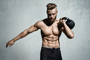 Young muscular man training with kettlebells. Photo of man with naked torso on grey background....