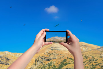 Female taking picture of landscape of mountain birds and sky on smart phone. Birds eagle flying above mountain in mobile phone. Day landscape