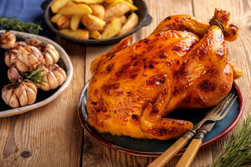 Roasted chicken  in a plate on a wooden table with garlic and potatoes.