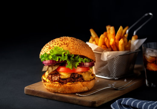 Tasty grilled beef burger with lettuce, cheese and onion served on cutting board on a black wooden table, with copyspace.