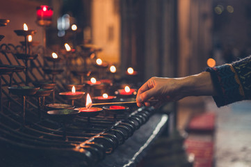 Hand of young woman lighting votice candles