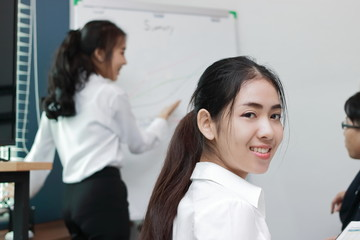 Cheerful young Asian business woman smiling between presentation in office.