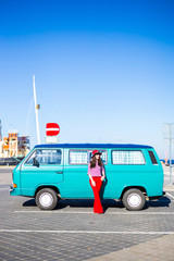 young woman in red with retro minivan