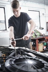 Young mechanic repair a car at a garage
