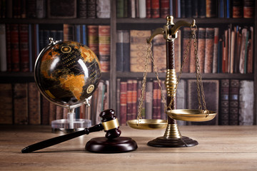Judge's Gavel and scales of justice and law books in the background