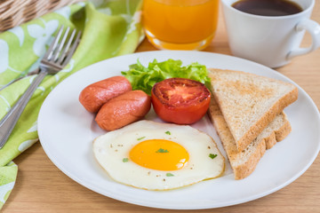Breakfast with fried egg, toast, sausage, vegetable, coffee and orange juice on table