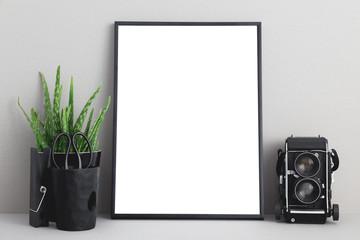 mock up blank photo frame with houseplant on shelf.