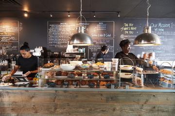 Fototapeta Staff Working Behind Counter In Busy Coffee Shop obraz