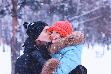 man carries a girl young couple in winter