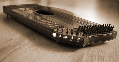 Old zither lying on a wooden table.