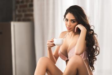 beautiful sexy young woman in lingerie holding cup of coffee and looking at camera