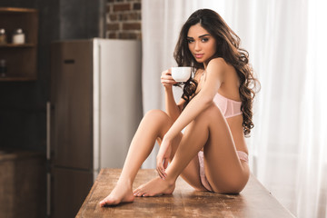 sexy young woman in lingerie holding cup of coffee and looking at camera