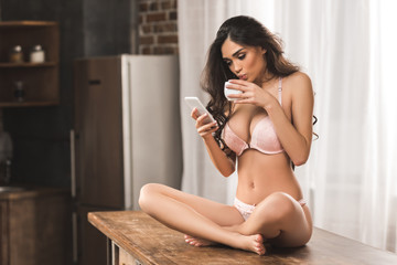 sexy young woman in underwear using smartphone while sitting on table and drinking coffee at home