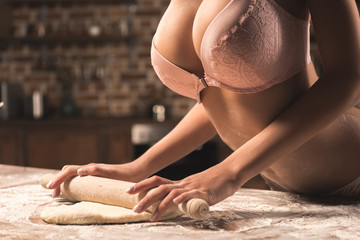 cropped shot of sexy young woman in underwear rolling dough with rolling pin in kitchen