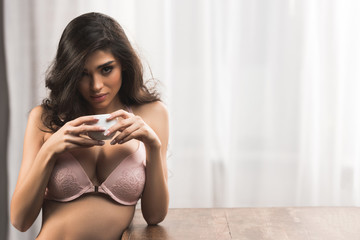 beautiful sexy woman in bra drinking coffee and looking at camera