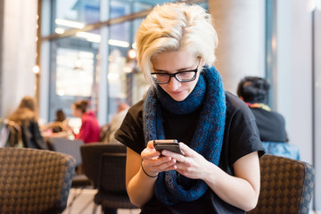 Young beautiful blonde woman in black glasses using telephone, sitting near window in modern city coffee shop