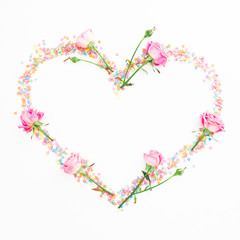 Heart made of pink flowers and candy confetti on white background. Flat lay, Top view. Valentine's day composition