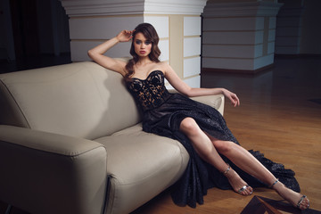 Full lenght portrait of gorgeous woman in the long black dress sitting on the sofa