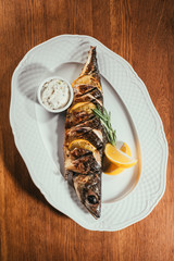 Top view of baked fish with lemon and herbs on white plate with sauce on wooden table