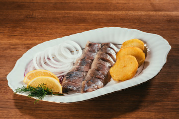 herring fish slices laying on plate with onion and orange slices over wooden table