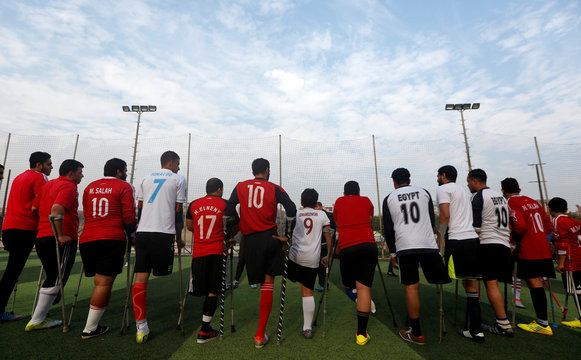 """Members of """"Miracle Team"""", a soccer team made up of one-legged, crutch-bearing soccer players, listen to their coach before a training session at El Salam club on the outskirts of Cairo"""