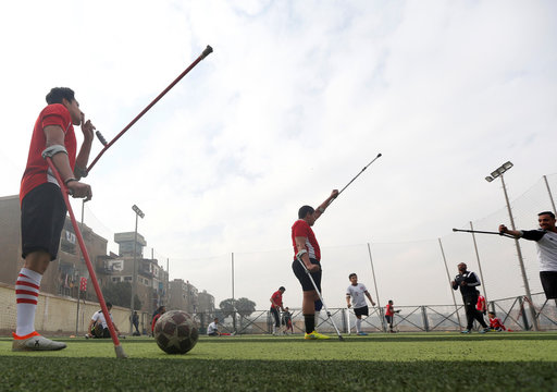 """Members of """"Miracle Team"""", a soccer team made up of one-legged, crutch-bearing soccer players, listen to their coach during a training session at El Salam club on the outskirts of Cairo"""