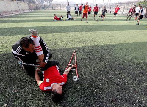"""Team coach Yousry Ibrahim, helps Mahmoud Tawfik, 28, captain of """"Miracle Team"""", a soccer team made up of one-legged, crutch-bearing soccer players, at El Salam club on the outskirts of Cairo"""