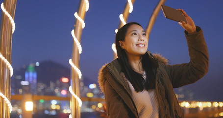 Asian woman taking photo on cellphone in the city of Hong Kong at night, bokeh city background