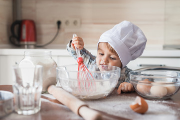 happy little kid in chef hat mixturing dough with whisk at kitchen