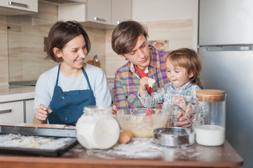happy young family preparing homemade cookies together