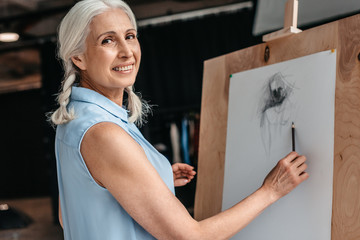 beautiful senior woman smiling at camera while drawing with pencil on easel at art class