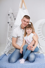 happy daughter hugging father in the kid bedroom. Happy family spending time at home.