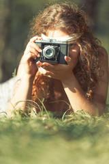 Pretty hippie girl on the grass taking photos with an old camera - Vintage effect photo