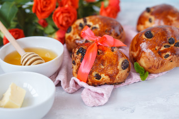 A beautiful breakfast, a date, buns with raisins, butter and honey, a bouquet of roses. Valentine's Day concept.