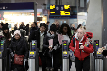 Commuters use ticket barriers to exit from London Bridge train station in London