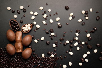 Easter concept painted and chocolate eggs, sweets, drops, candys, bunny for holiday with place for text pattern on wooden dark black background