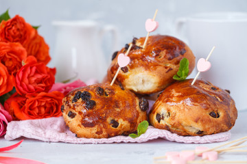 Breakfast for Valentine's Day. Buns with raisins, butter and honey, a bouquet of flowers. Valentine's Day concept.