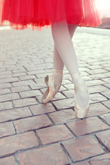 Ballet dancer's feet dancing on street. Young ballerinas in red tutu. Ballet feet on the point on red brick.