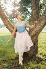 Ballet dancer dancing on street. Young ballerina in pink tutu. Pretty ballerina in the park doing exercise on tree.