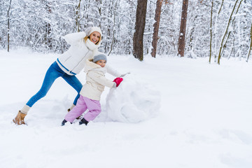 happy mother and daughter making snowman and smiling at camera in winter park