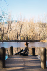 Sensual woman on autumnal pier above pond