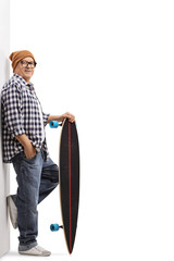 Old hipster with a longboard leaning against a wall