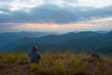 A tourist sitting on peak of mountains and enjoy to see beautiful landscape view of sunset, hiking tourist adventure on vacation on mountains