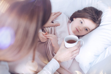 Do not be so serious. Kind brunette female sitting near her child while giving cup with tea to make her feel better
