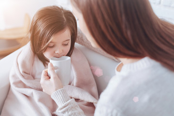 Tasty tea. Attractive brunette holding white cup in left hand and looking at her daughter while sitting in front of her